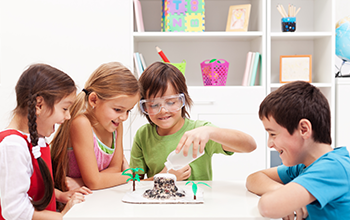 2 boys and 2 girls gathered around a table while one boy is pouring water into a structure to make a volcano