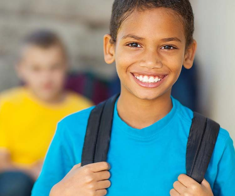 Boy in blue shirt smiling wearing a black strapped schoolbag.