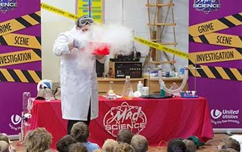 Mad scientist blowing into a red bowl with smoke coming out of it while kids watch