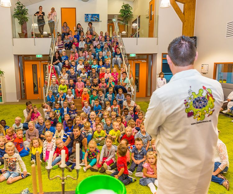 Mad scientist performing in front of kids sitting on the floor and up the stairs
